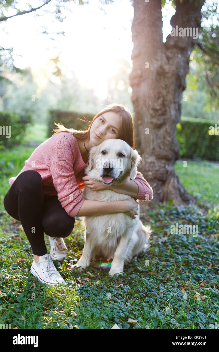 Photo of girl hugging dog on lawn - Stock Image