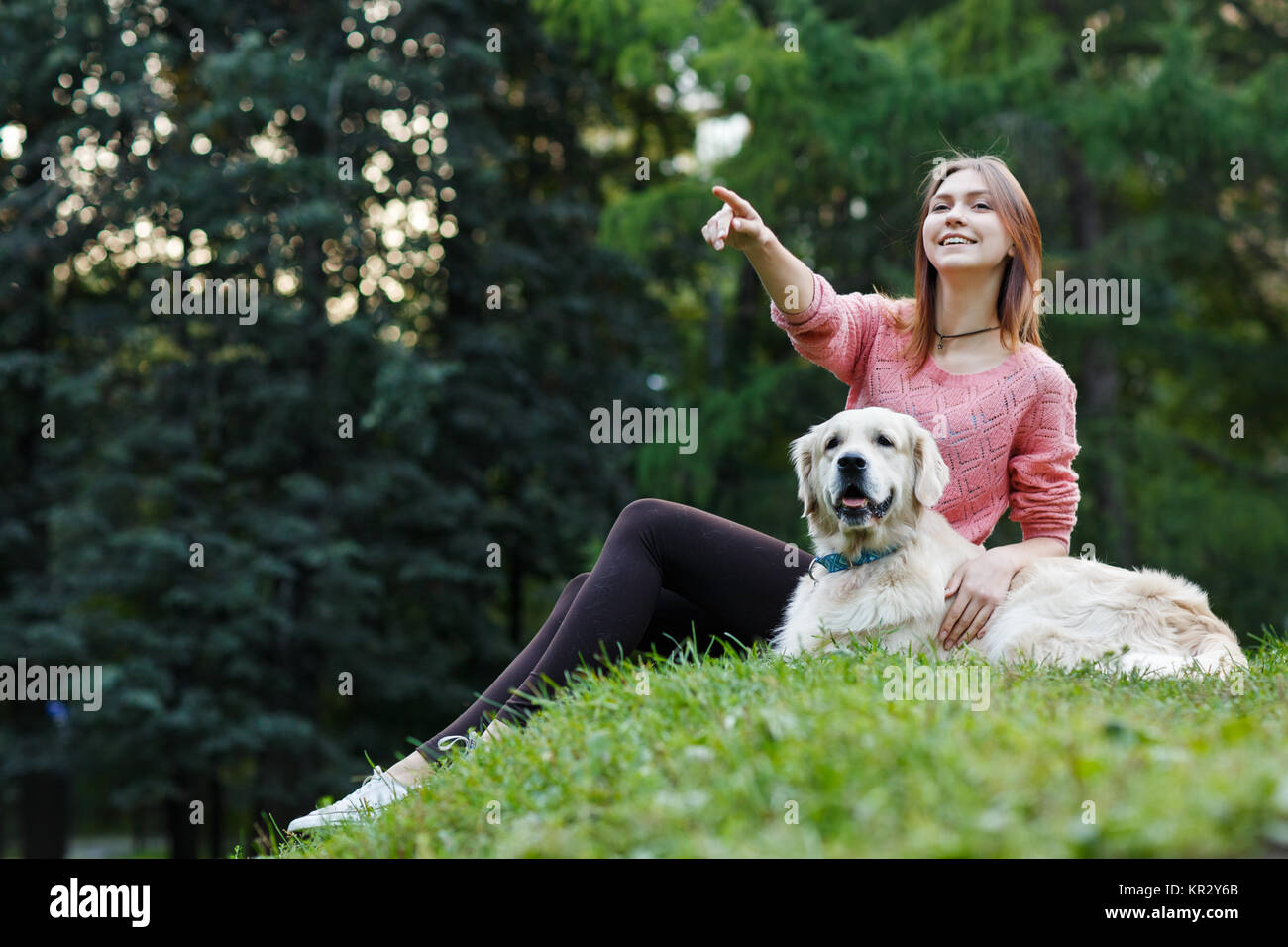 Image from below of woman pointing forward next to dog on green lawn - Stock Image