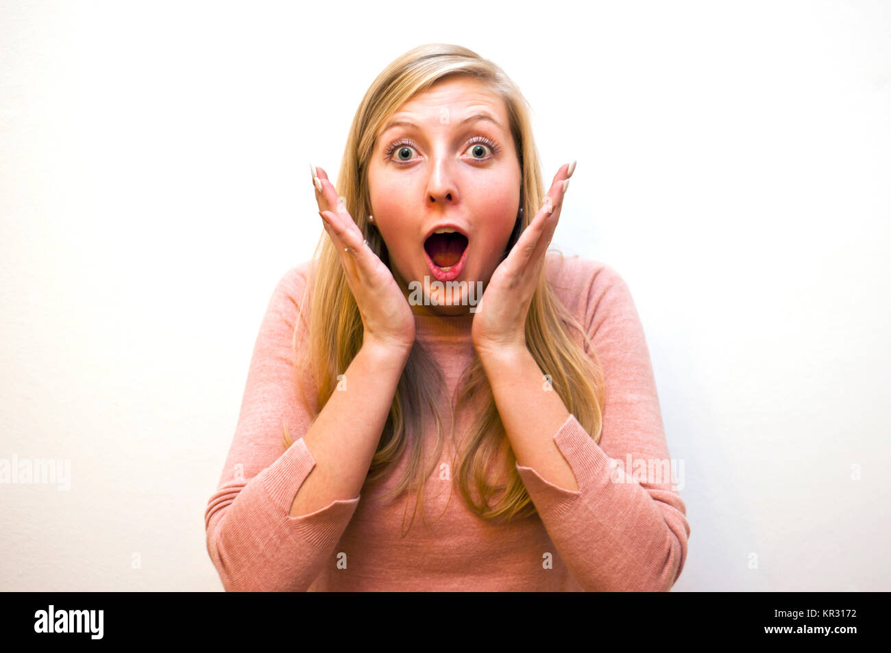 blond Caucasian girl with an expression of marvel and surprise - Stock Image