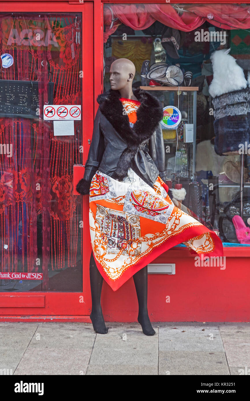 London, Lewisham  A gust of wind catching the skirts of a tailor's dummy outside a shop in Deptford High Street - Stock Image