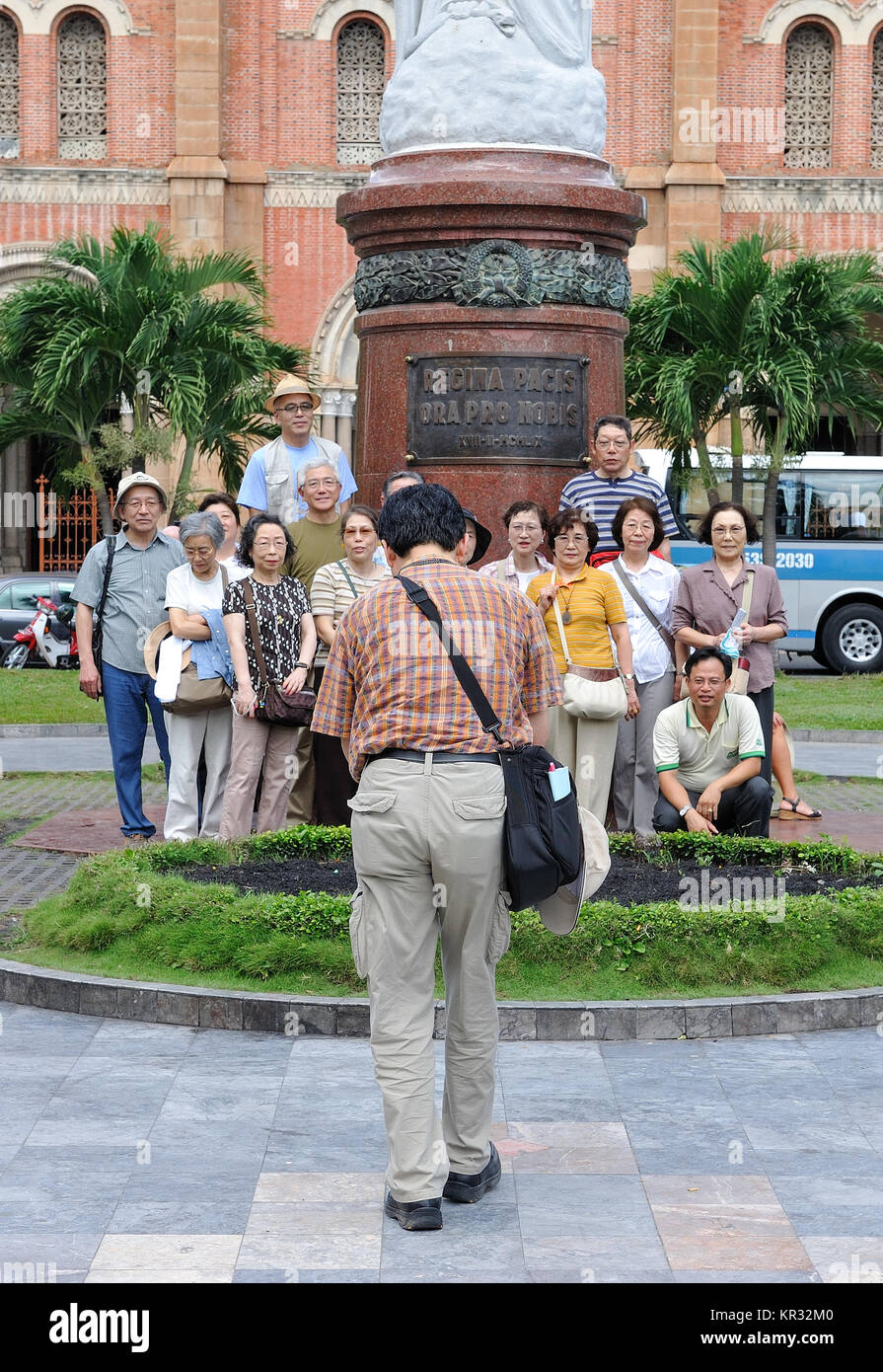 Group of tourists posing outside Notre Dame cathedral in Saigon.  Notre Dame is one the icons of Saigon and was - Stock Image