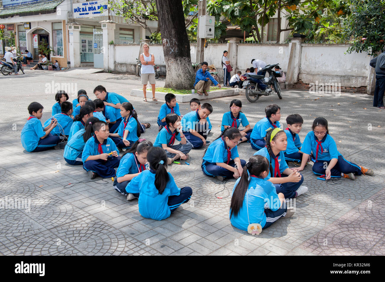 School children resting on a street in Ho Chi Minh City. - Stock Image
