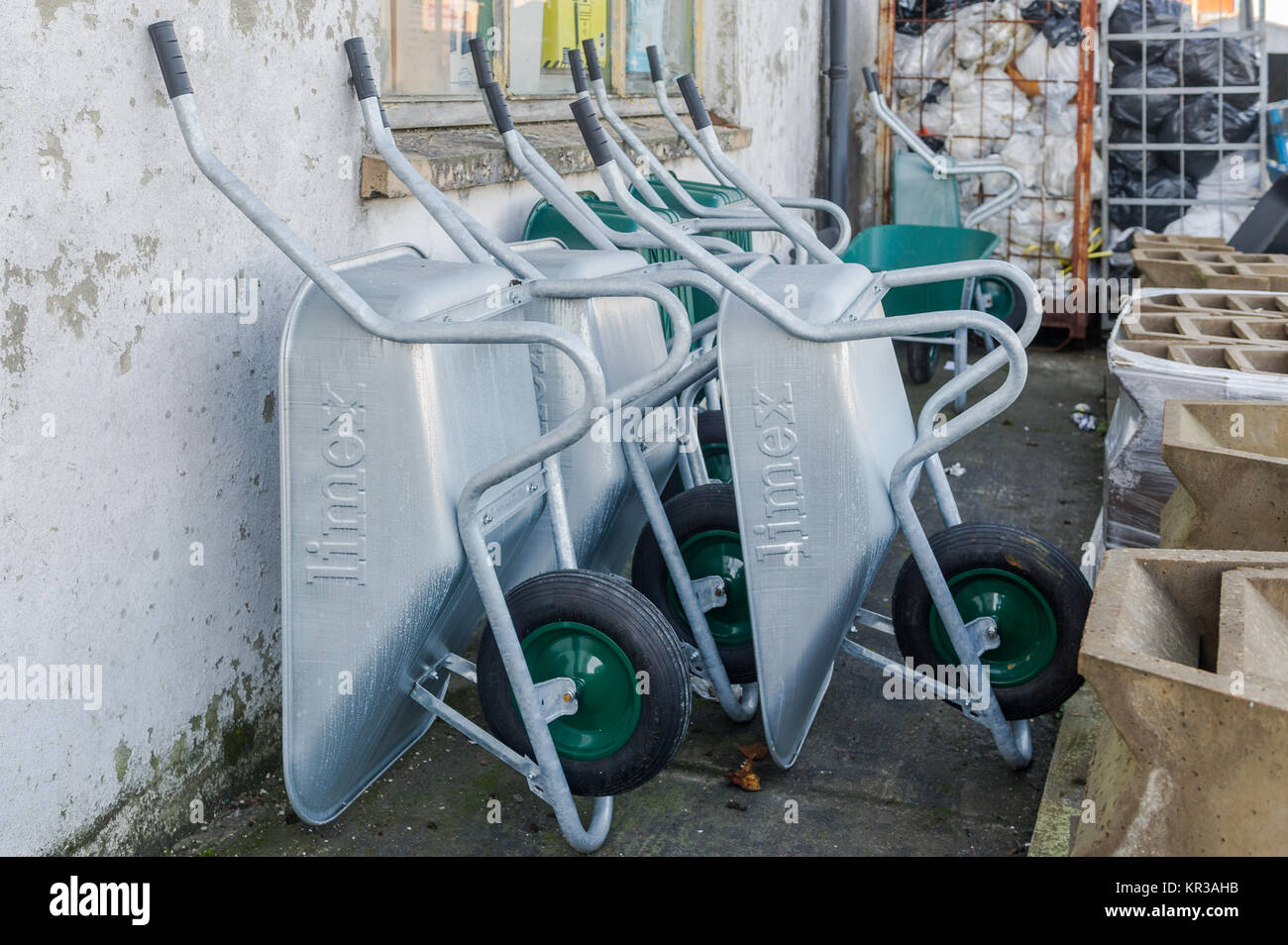 Wheelbarrows for sale against the wall of a builders merchants, Ireland. - Stock Image