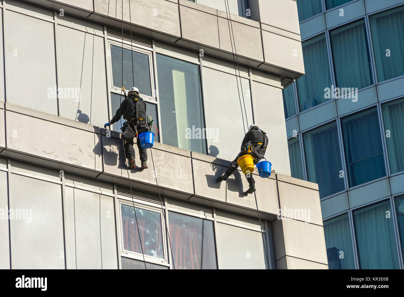 Two window cleaners using rope access techniques on a building near the Bull Ring, Birmingham, England, UK, - Stock Image