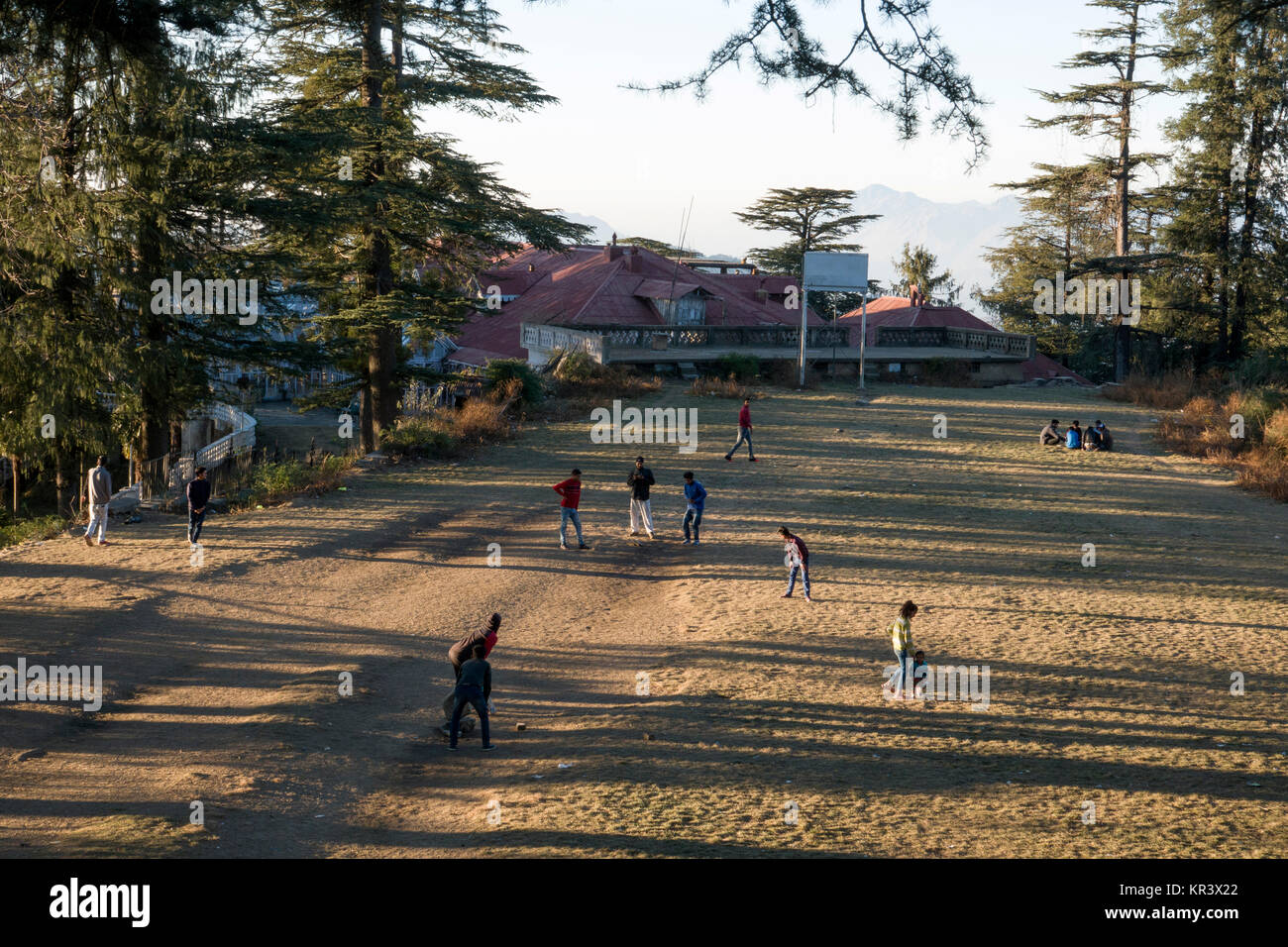 Teenage boys playing game of casual cricket in park at Shimla, India - Stock Image