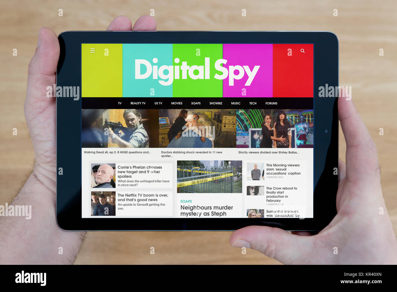 A man looks at the Digital Spy website on his iPad tablet device, shot against a wooden table top background (Editorial - Stock Image