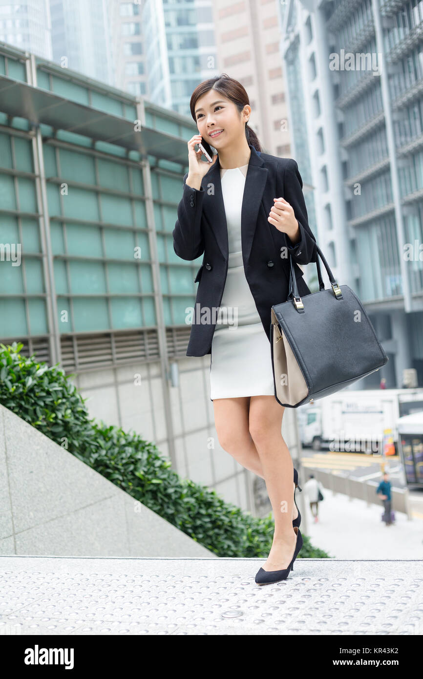 Young Business woman walking out of office and talk to phone - Stock Image