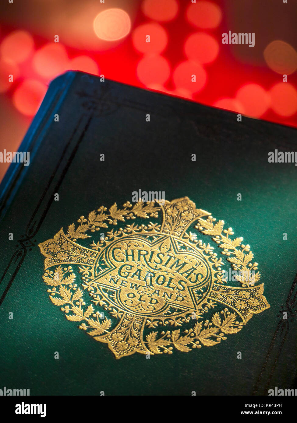 'Christmas Carols Old and New'  music book cover with warm inviting festive Christmas lights behind - Stock Image