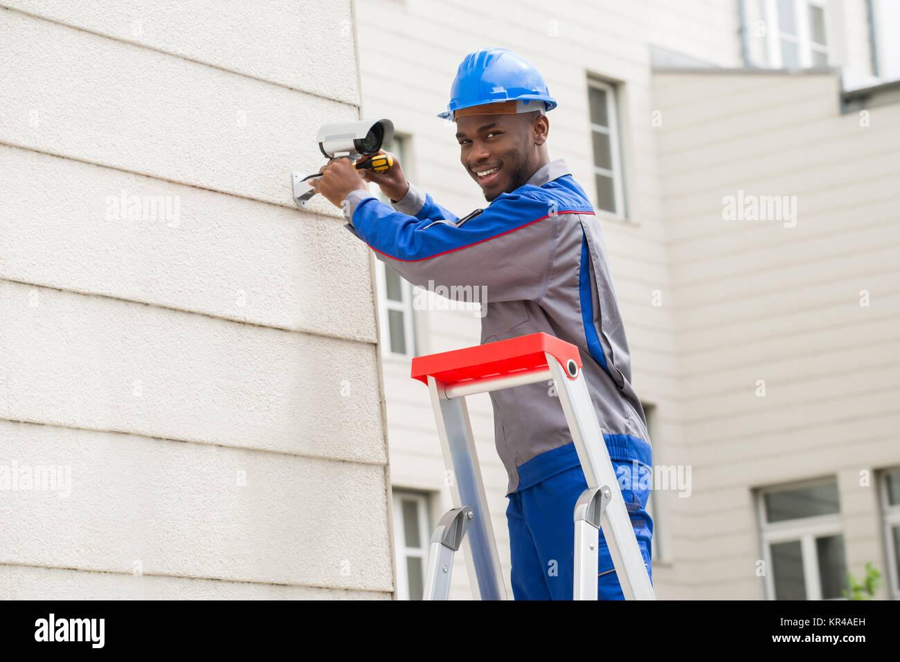 Male Technician Repairing Camera - Stock Image