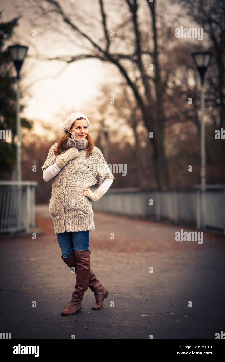 Autumn/winter portrait: young woman dressed in a warm woolen cardigan posing outside in a city park Stock Photo