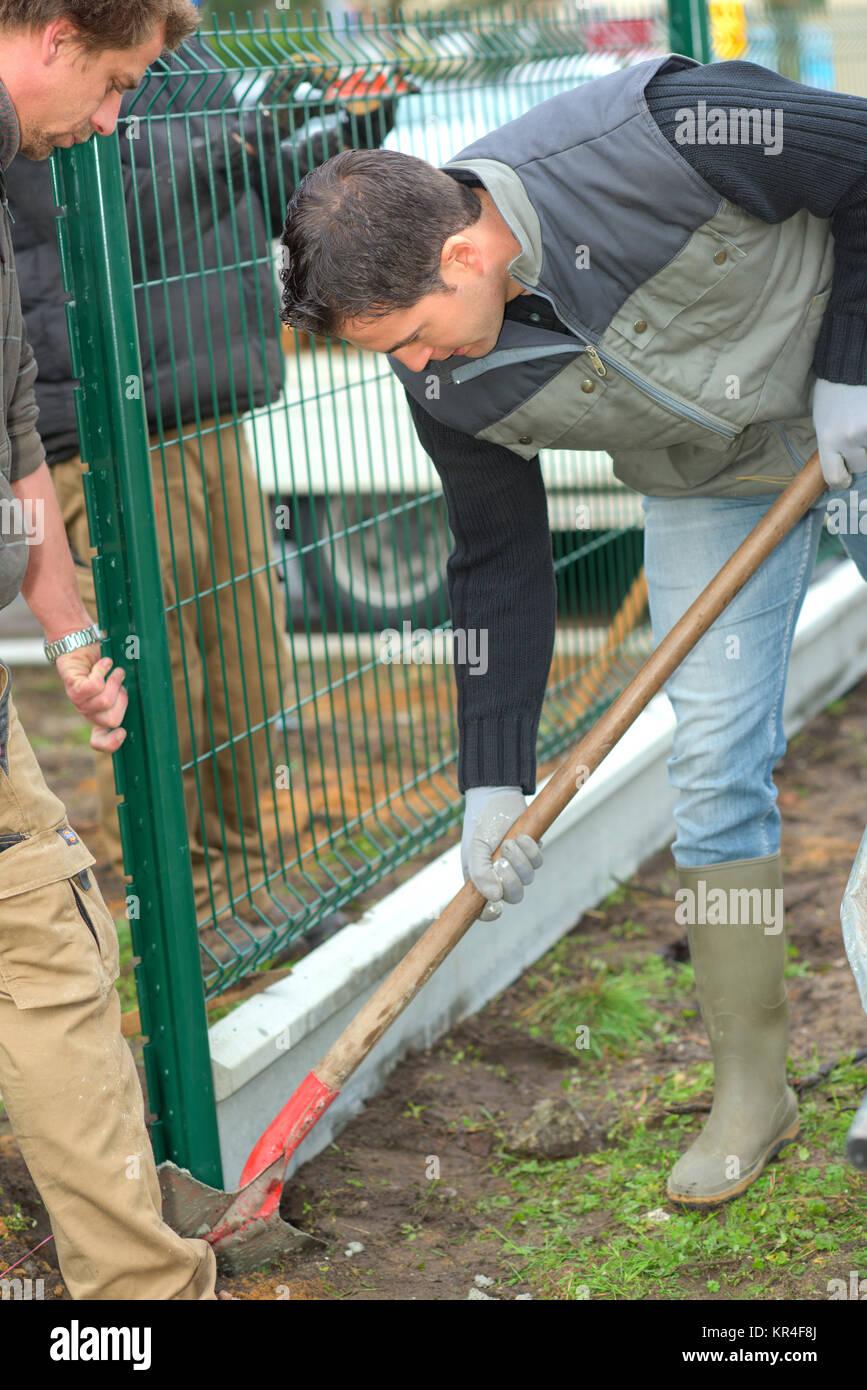 Gardeners putting up a perimeter - Stock Image