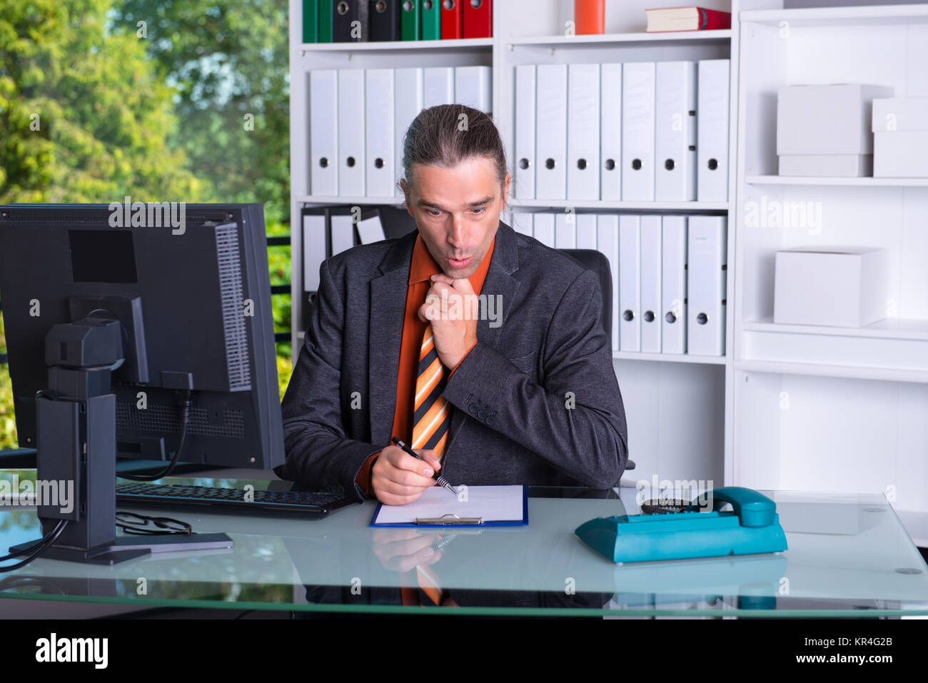 business man at his desk is amazed - Stock Image