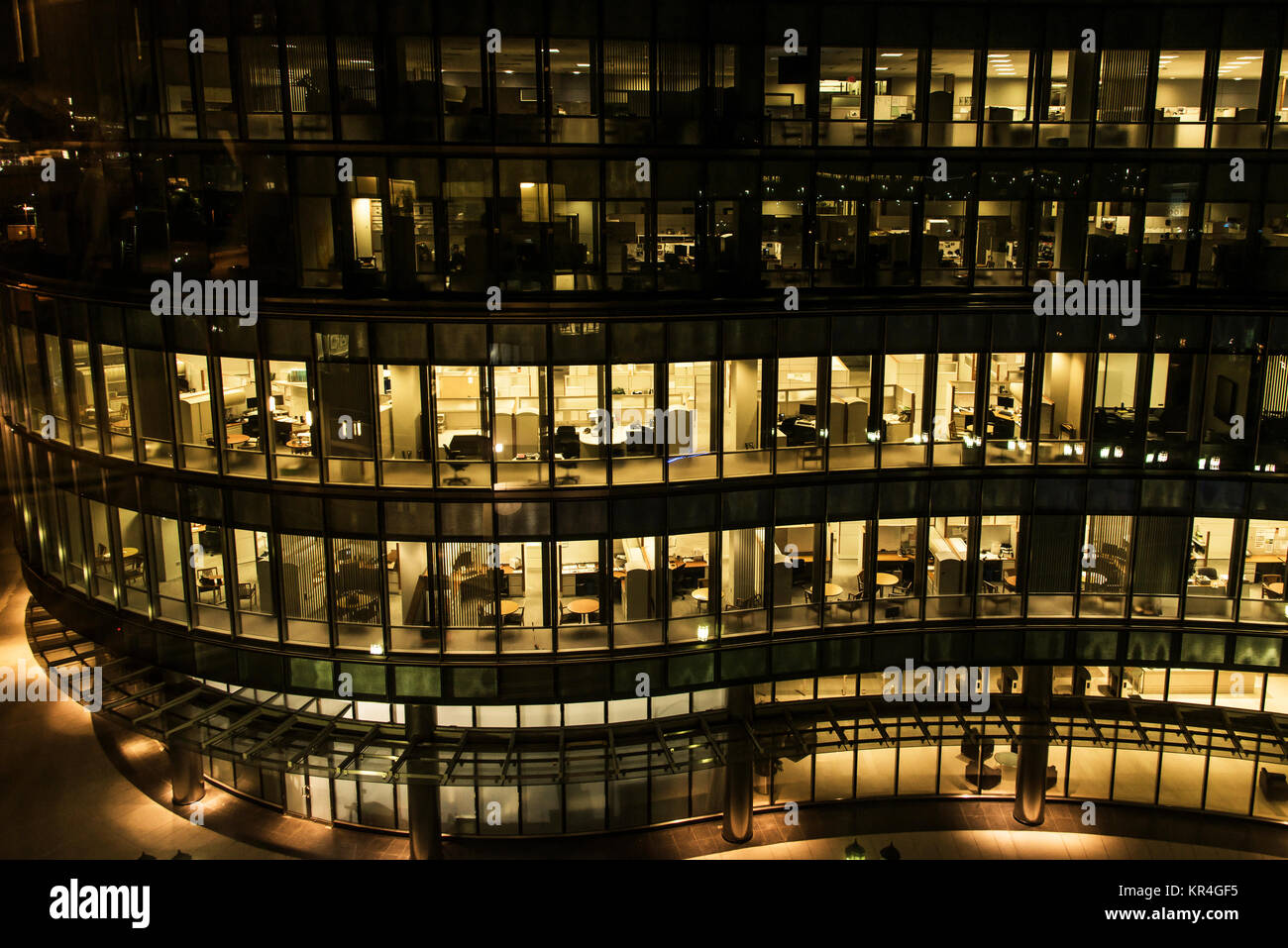 yellow light windows of an office building at night in Boston late night at work glass curtain wall office building Stock Photo