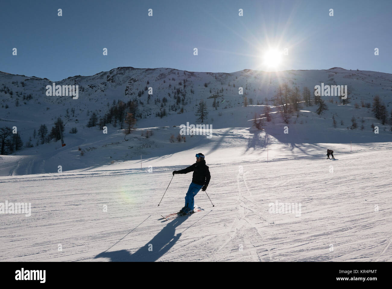Skier skiing downhill during sunny day in high mountains  at Sauze D'Oulx Piedmont Italy - Stock Image