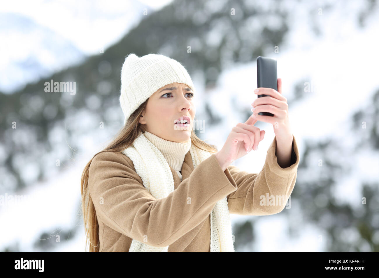 Desperate woman searching mobile phone coverage in winter holidays in a snowy mountain - Stock Image