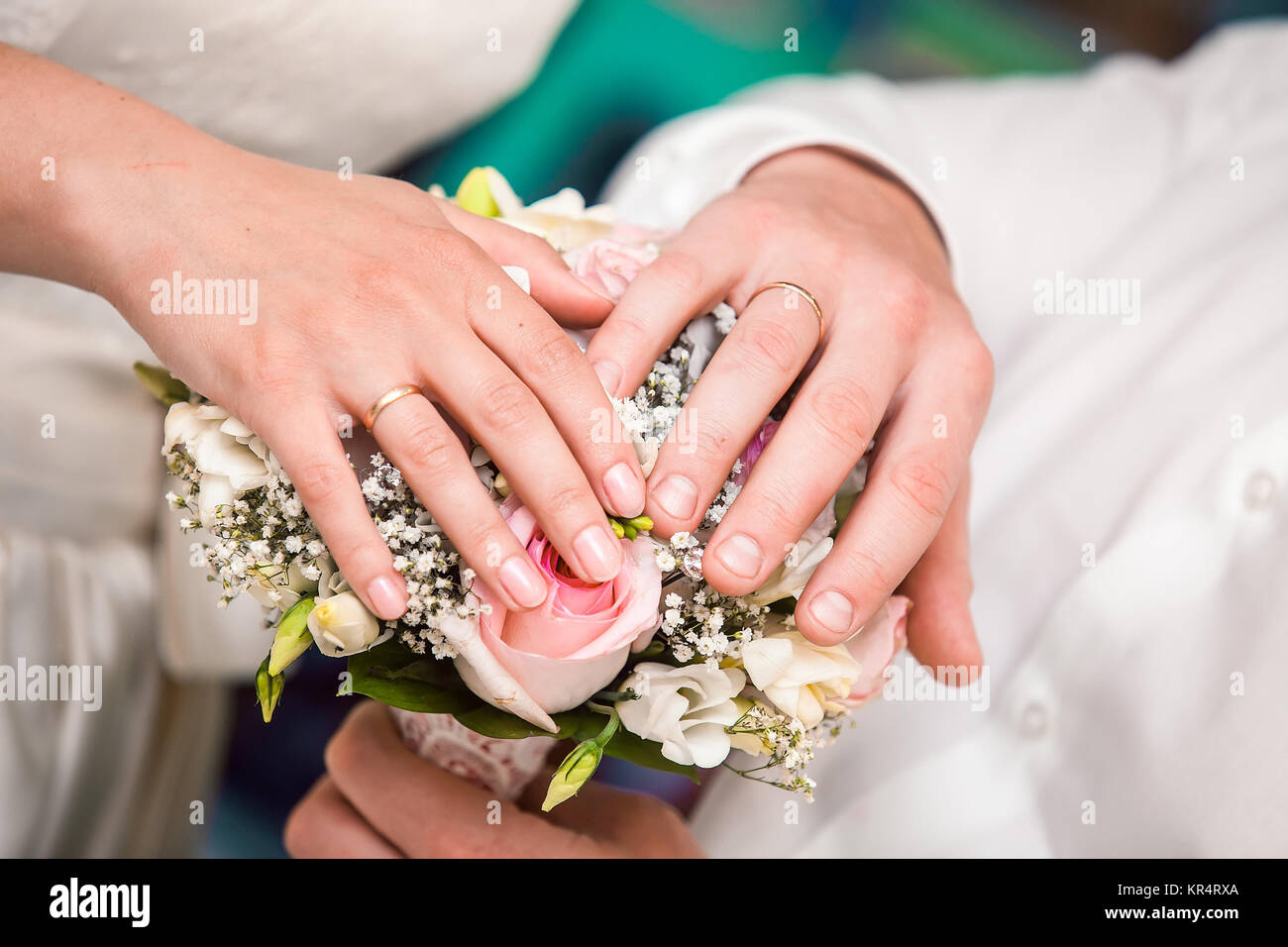 Hands of the groom and the bride with wedding rings and a wedding ...