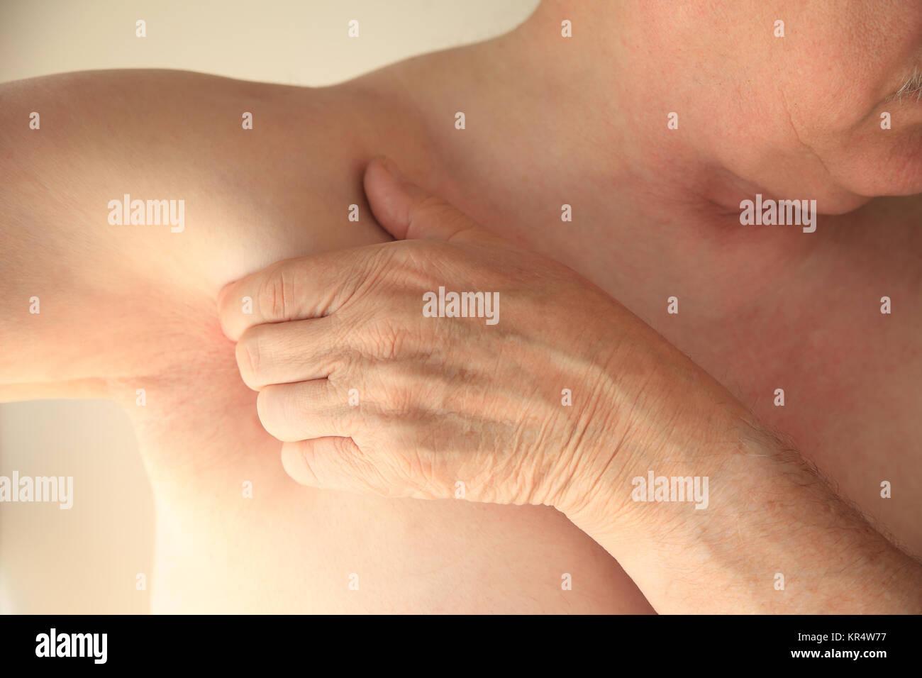 Senior man with pain next to armpit - Stock Image