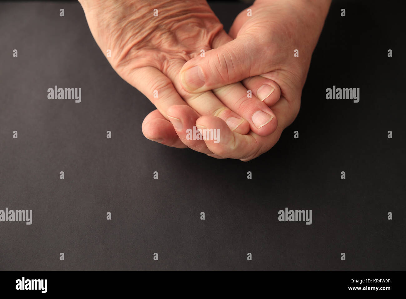 Older man grips his numb fingers - Stock Image