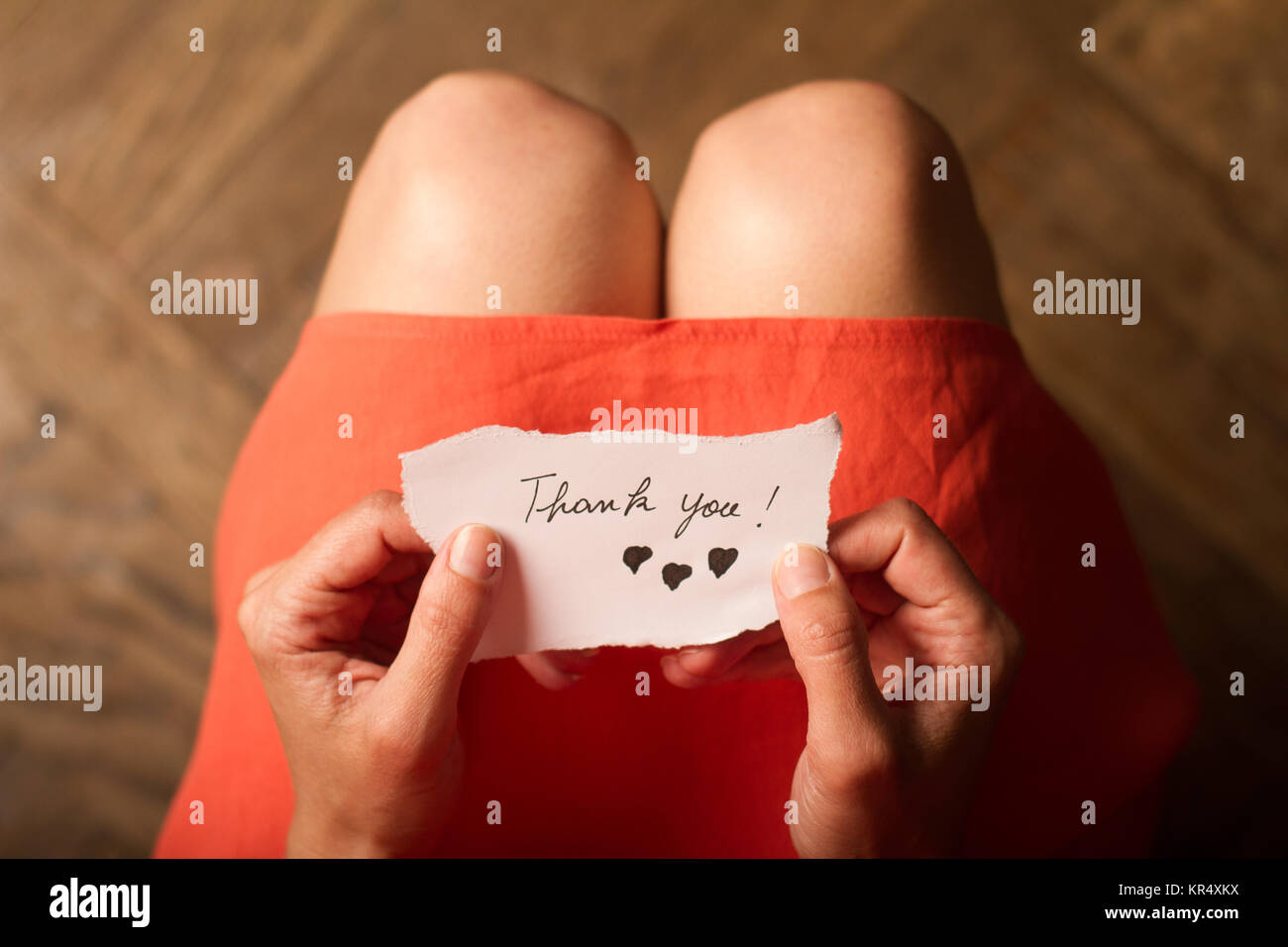 Woman holding a thank you note in her hand - Stock Image