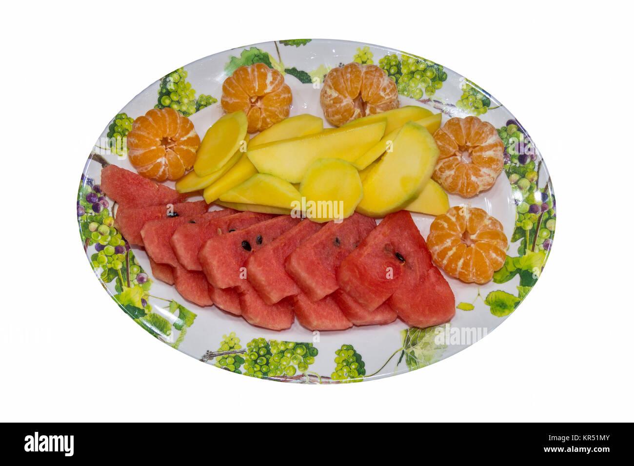 Plate of fruit - mandarins, mango, water melon isolated on white background - Stock Image