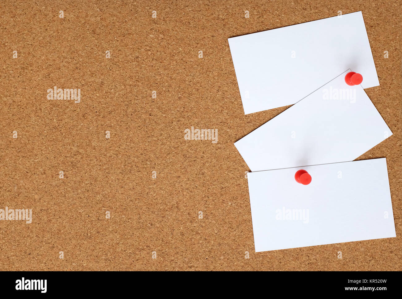 Cork board with three white cards pinned to it - Stock Image
