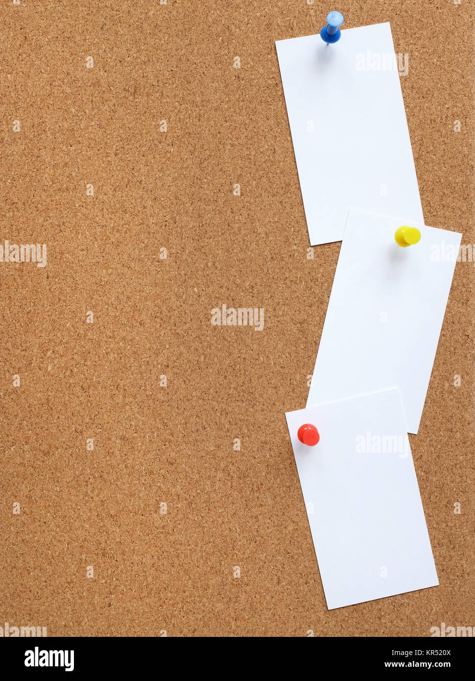 Cork noticeboard with three white cards pinned vertically - Stock Image