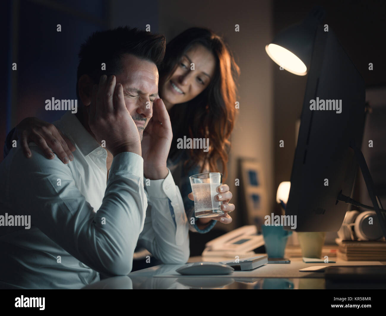 Man working with his computer and having a bad headache, his wife is giving him a painkiller and comforting him - Stock Image