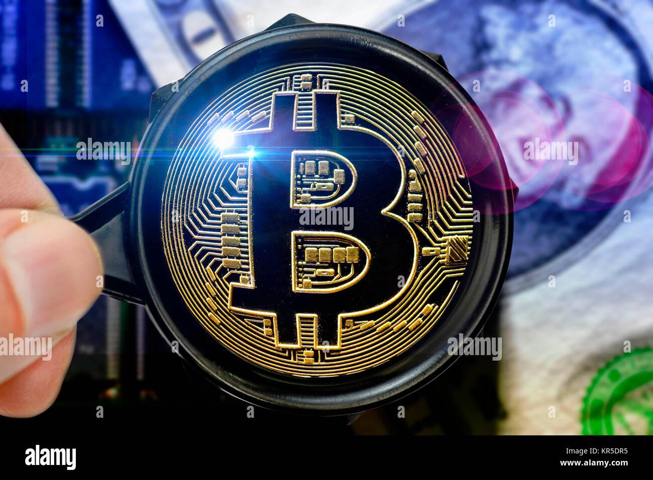 Coin with Bitcoin sign under the magnifying glass, Münze mit Bitcoin-Zeichen unter der Lupe Stock Photo