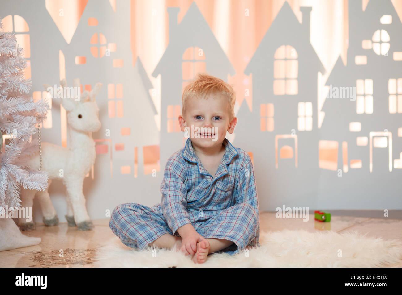 Cute blonde hair little boy in sleepwear near christmas toy paper houses. - Stock Image
