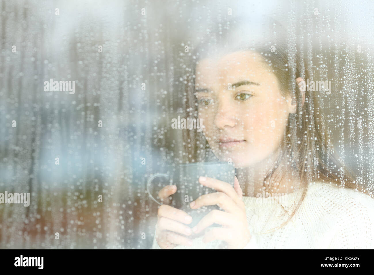Portrait of a longing teen looking through a window alone at home in a rainy day - Stock Image
