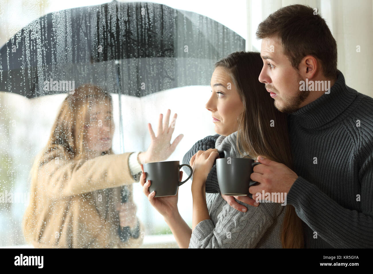 Stalker ex girlfriend disturbing to a couple that is relaxing looking through a window in a coffee shop - Stock Image