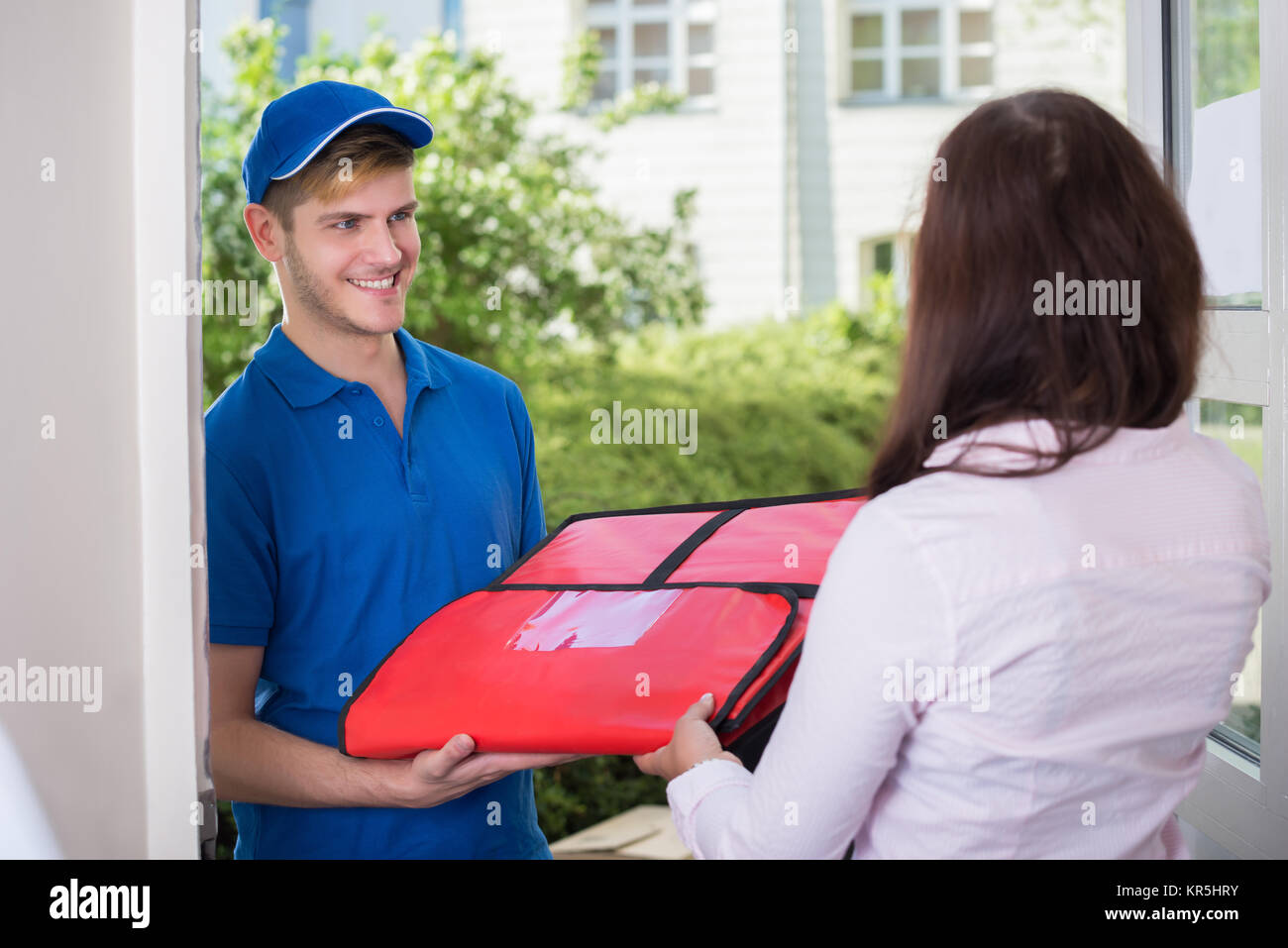 Man Delivering Pizza To Young Woman - Stock Image