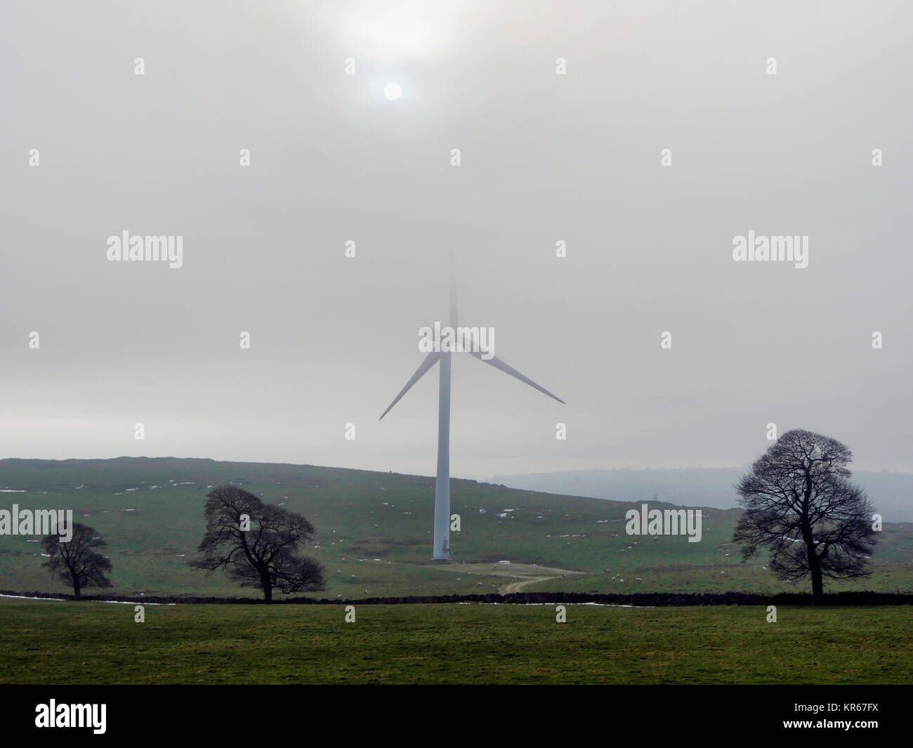 Brassington, Derbyshire. 19th December, 2017. UK Weather wind turbines turning in the cold mist near Brassington, - Stock Image