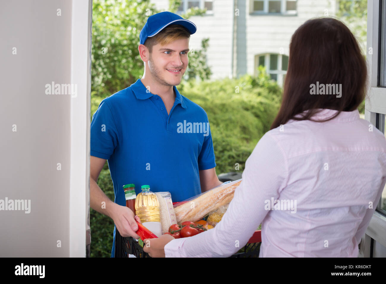 Smiling Young Woman Delivers Groceries - Stock Image