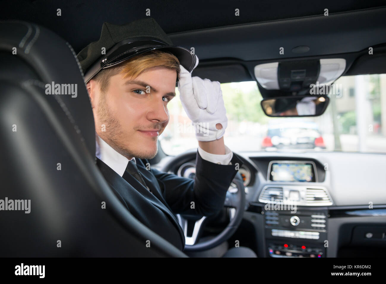 Portrait Of Smiling Young Chauffeur In Car - Stock Image