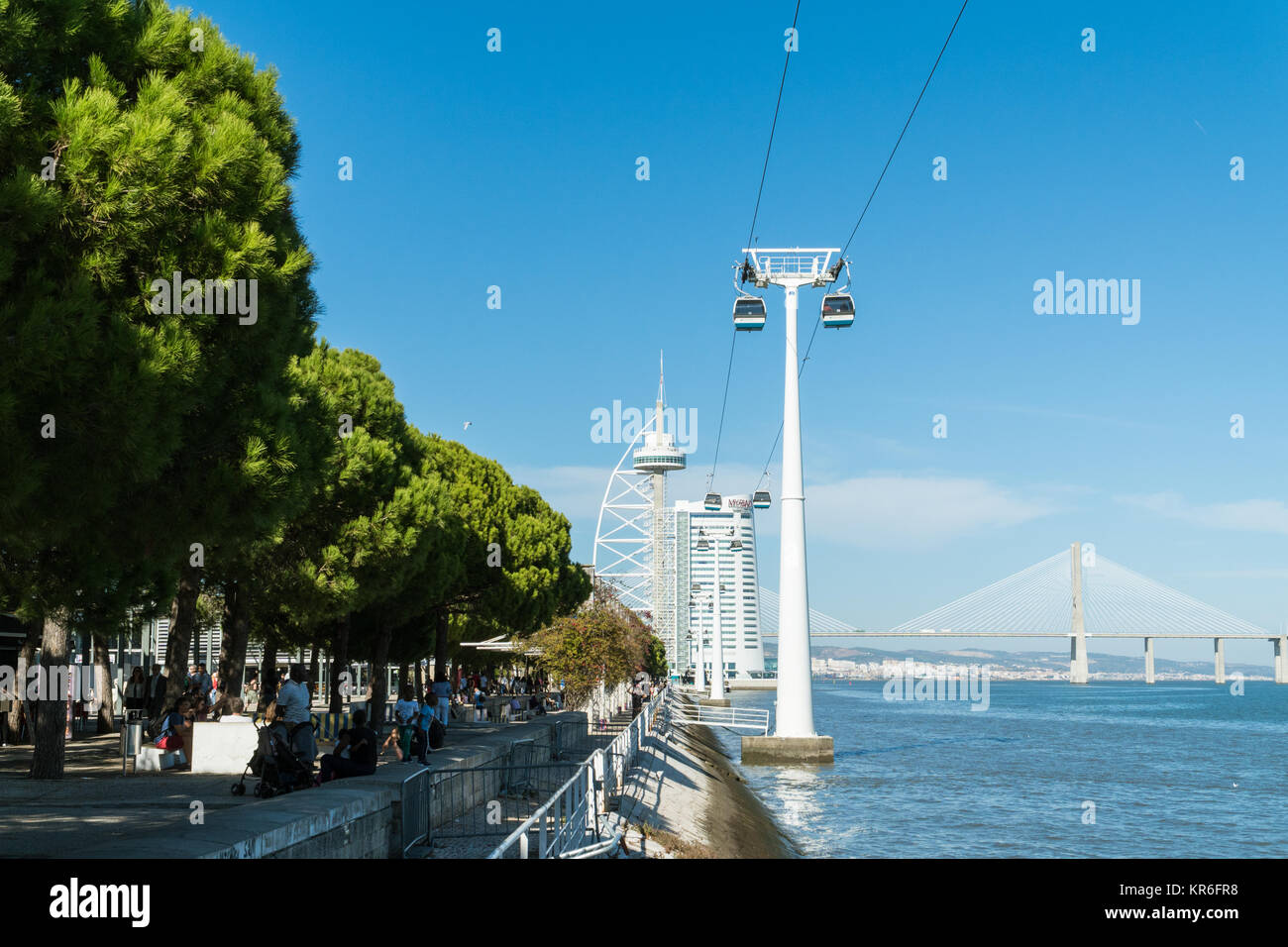 Lisbon, Portugal - 30 October 2017: Telecabines (cable cars) over Passeio das Tagides park and people walking by - Stock Image