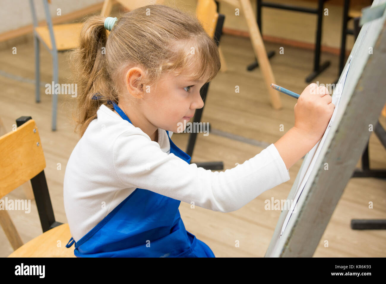 Five-year girl paints on an easel in the drawing lesson - Stock Image
