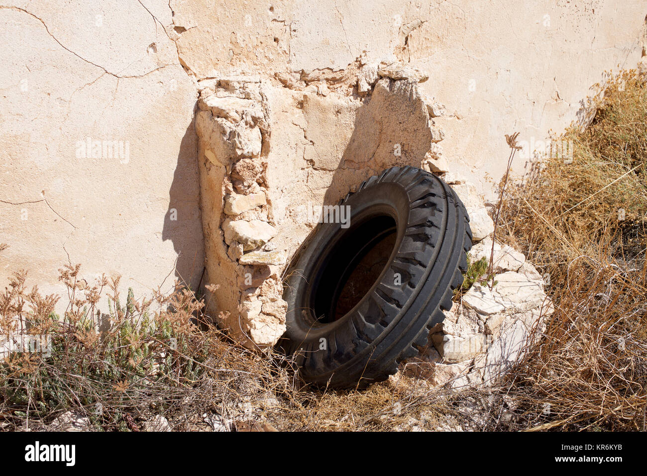 Tyre thrown away and leaning on a  wall in the sunshine - Stock Image