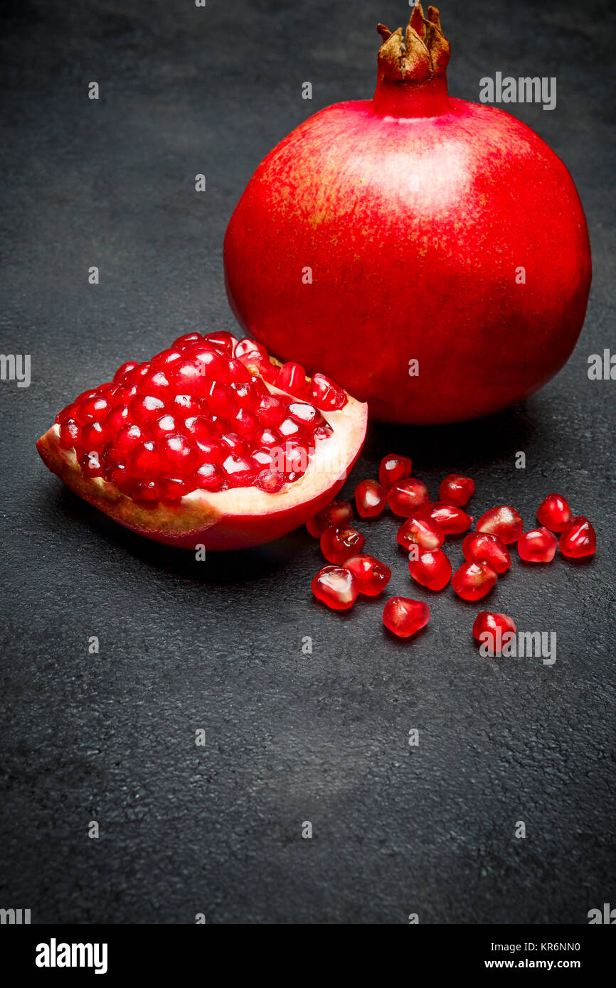 Pomegranate and seeds close-up on dark concrete background - Stock Image