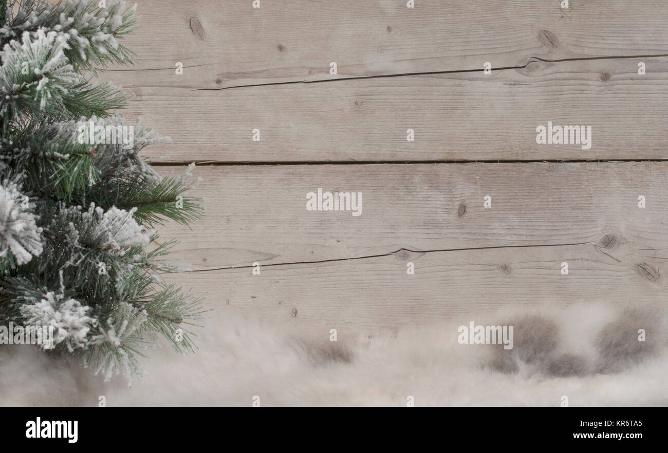 winter scenery background, with sheepskin, snowy tree and weathered wood backdrop - Stock Image