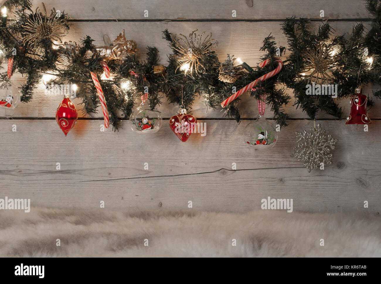 Christmas pine tree garland with red baubles, candy canes and ornaments, hanging on old wooden board background, - Stock Image