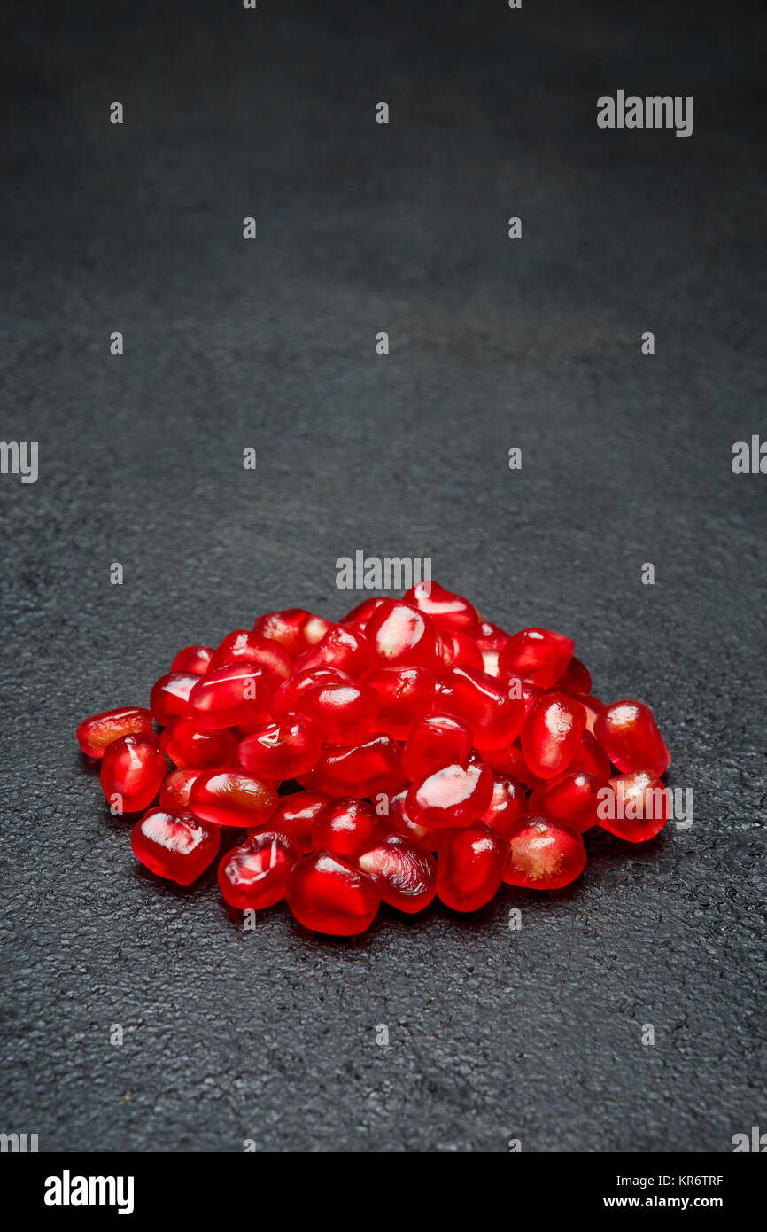 Pomegranate seeds close-up on dark concrete background - Stock Image