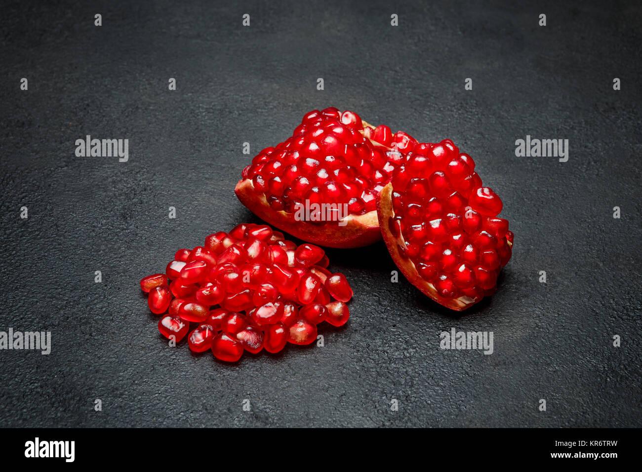 Pomegranate seeds close-up on dark concrete background - Stock Image