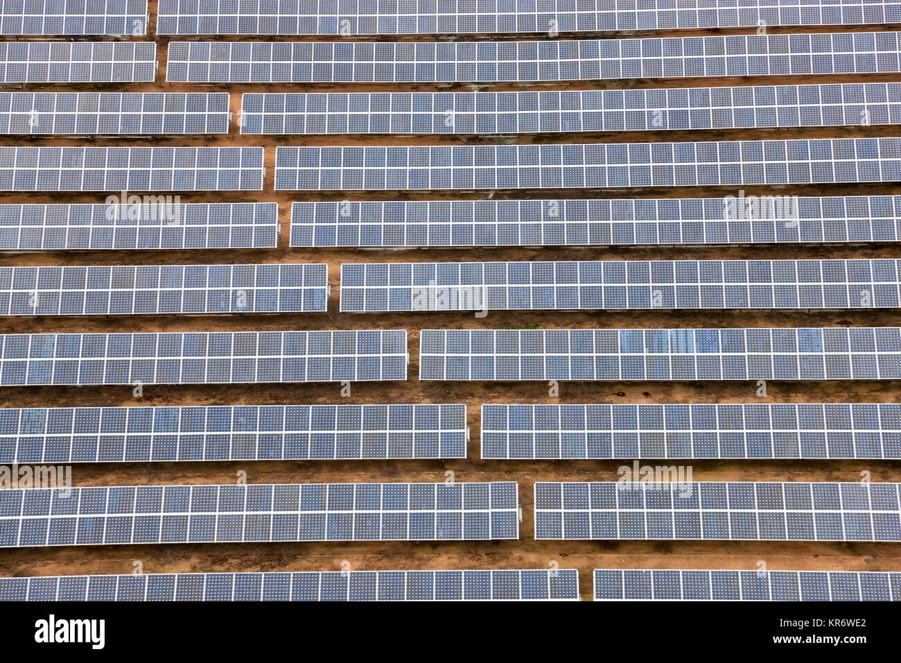 Aerial view of long rows of solar panels in the desert. - Stock Image