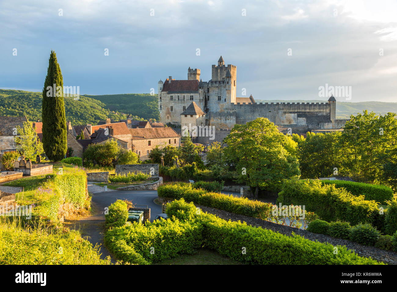 Landscape with trees, hedges and medieval castle with graveyard in the mid distance. - Stock Image