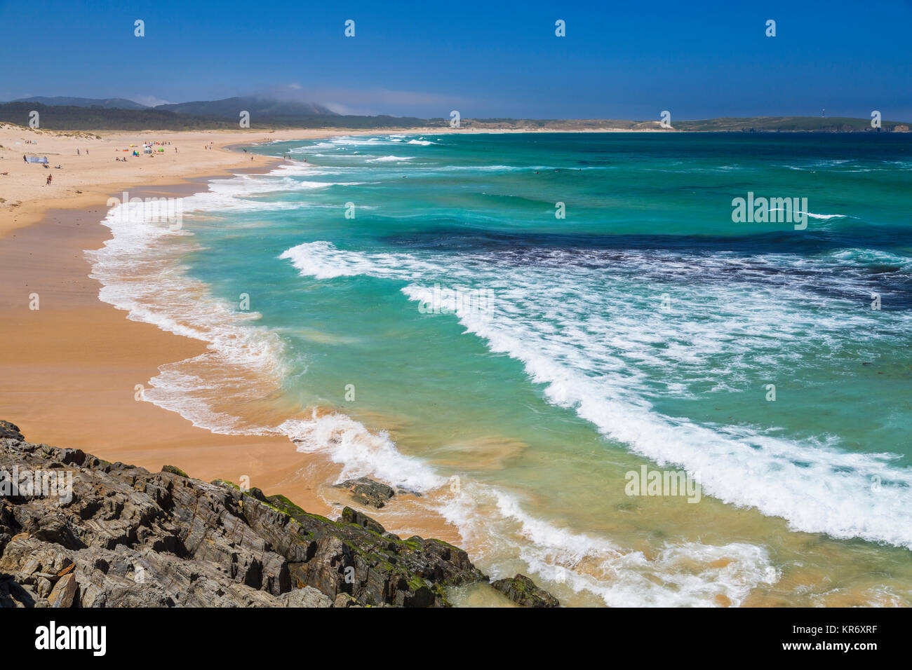 High angle view from cliff along long sandy beach. - Stock Image
