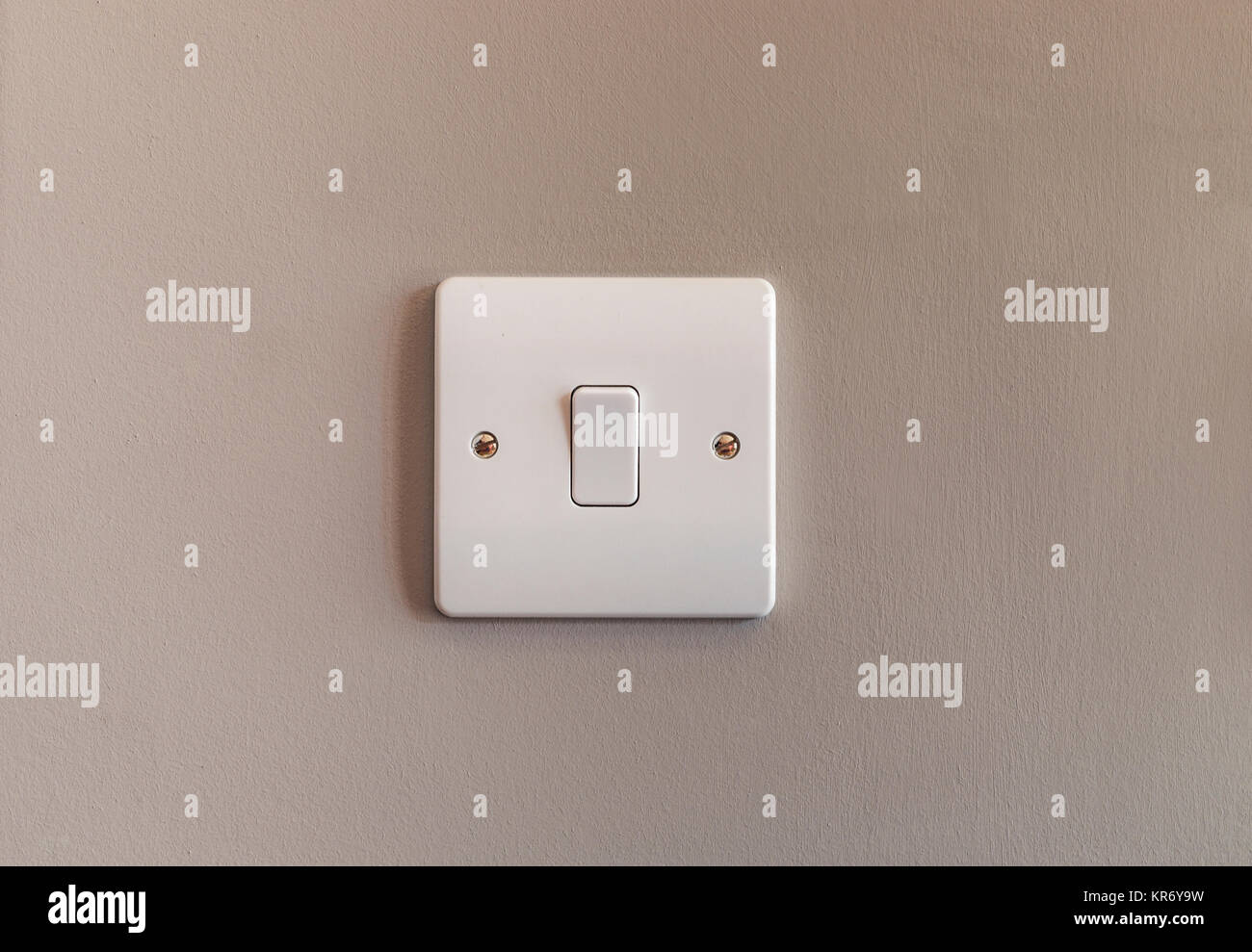 UK domestic single light switch in white plastic on a buscuit coloured wall - Stock Image