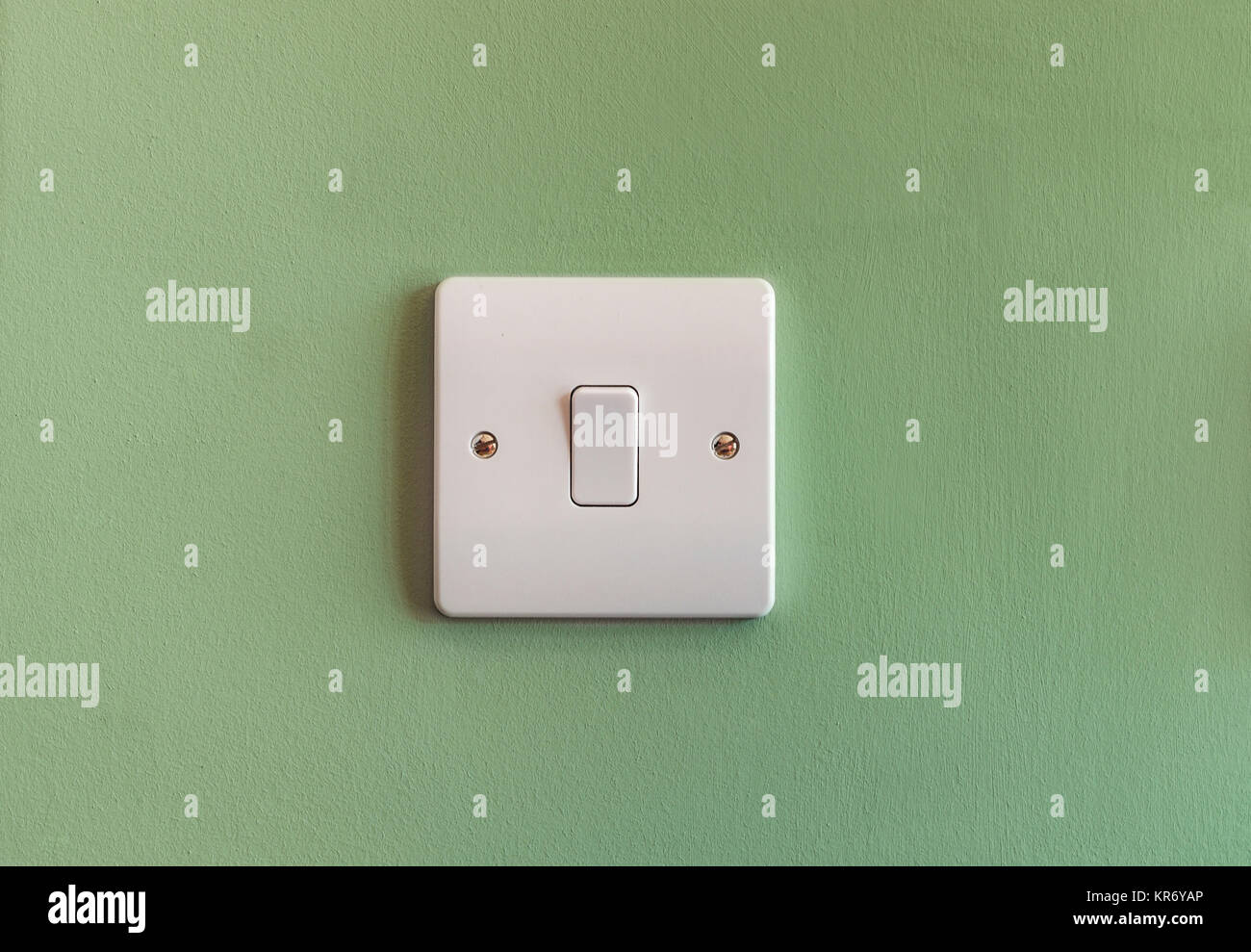 UK domestic single light switch in white plastic on a green coloured wall - Stock Image