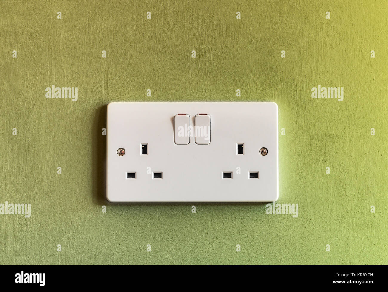 UK domestic 3 pin double plug electrical socket in white plastic on a green coloured wall - Stock Image