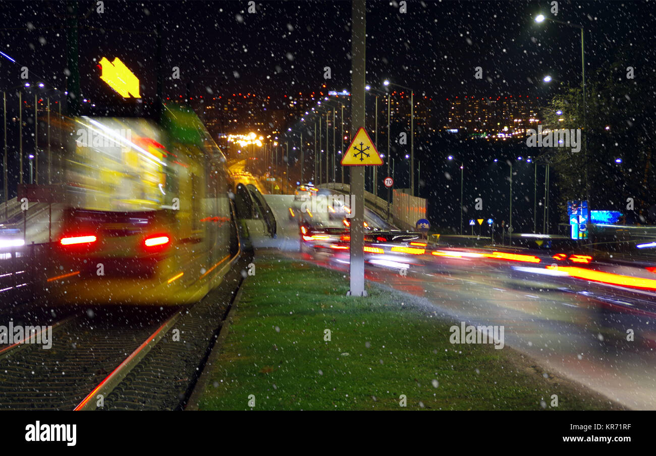 First snowfall in city by night. Blurred lights cars and tramway on town street with snowflakes in first plan. - Stock Image